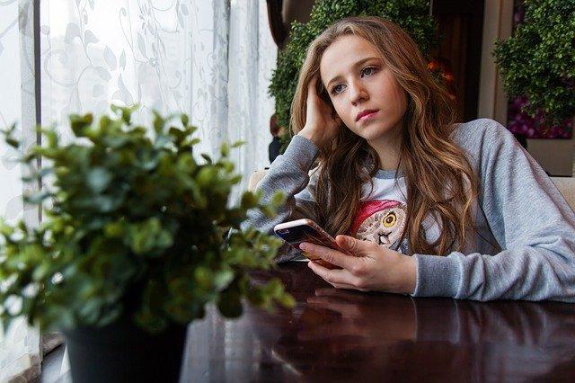Sad Girl Holding a Mobile Phone