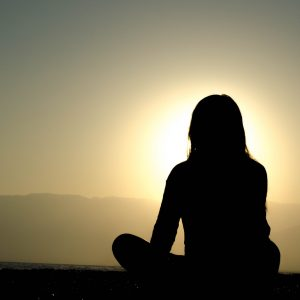 The back of a woman sitting and meditating at sunrise