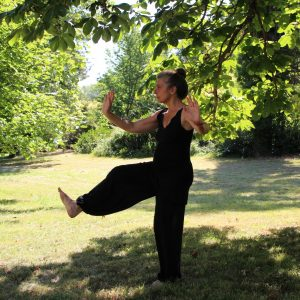 A woman in black pants and a black vest doing tai chi outdoors under a tree